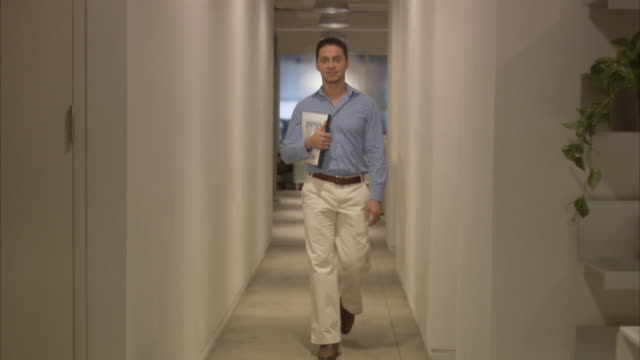 Young businessman carrying reports in office corridor, smiling / New York City, New York, USA