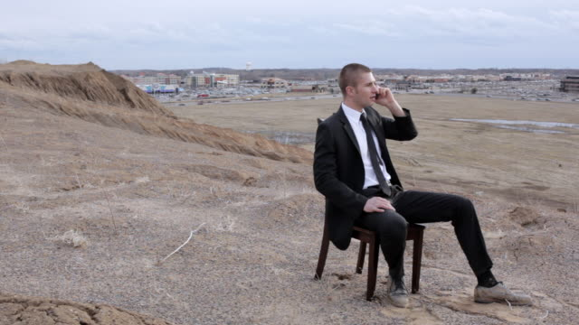 vidéos et rushes de ms young businessman dressed in  black suit  sitting on  chair and talking on cell phone on top of  bluff in  rural area / maple grove, minnesota, united states - voix