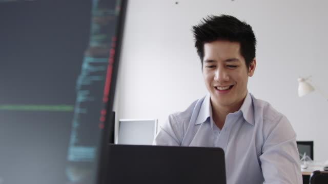 vídeos y material grabado en eventos de stock de joven empresario disfrutando trabajando en su escritorio - aprendiz