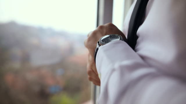 vidéos et rushes de jeune homme d'affaires s'habillant, mettant la montre de poignet sur sa main tout en restant près de la fenêtre - vêtement de peau