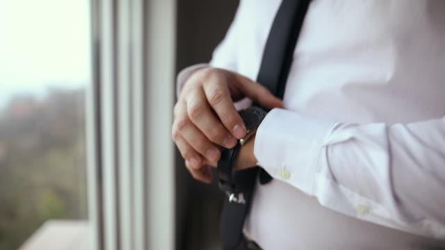 vídeos de stock e filmes b-roll de young businessman getting dressed, putting wrist watch on his hand while standing near window - calçada