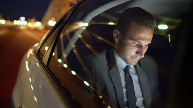 ms young businessman greeting someone while driving in the back seat of a car - smart phone video stock e b–roll