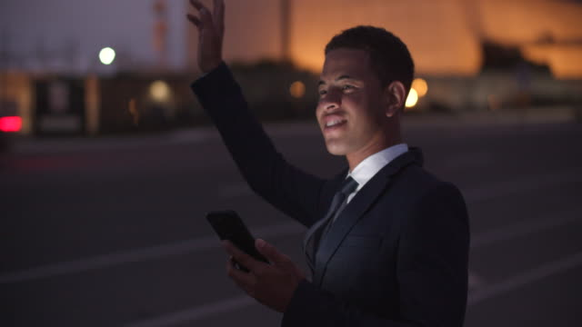 young businessman hailing a taxi on the street at night - full suit stock videos & royalty-free footage