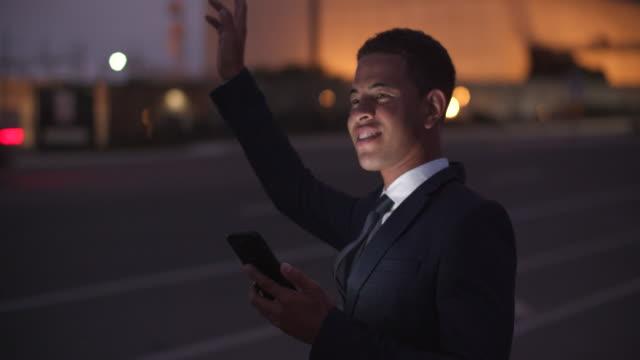 vídeos de stock e filmes b-roll de young businessman hailing a taxi on the street at night - negócio empresarial