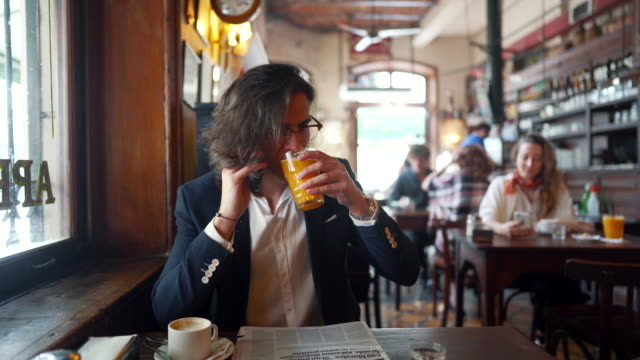 vidéos et rushes de jeune homme d'affaires ayant une conversation sur le téléphone portable et le jus potable au café local - tasse à café