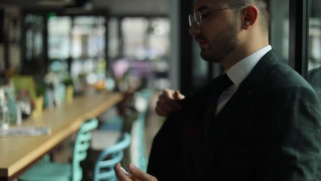 vídeos de stock e filmes b-roll de a young businessman in a suit applies perfume before meeting with clients. well dressed man applying perfume - desodorante