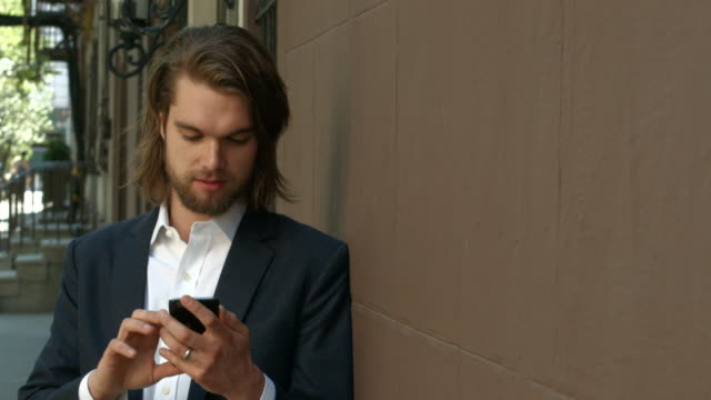 A young businessman in a suit texting and searching his cell phone outside in New York City