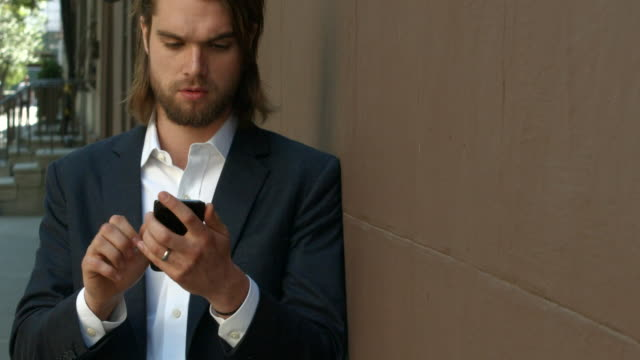 a young businessman in a suit texting and searching his cell phone outside in new york city - leaning stock videos & royalty-free footage