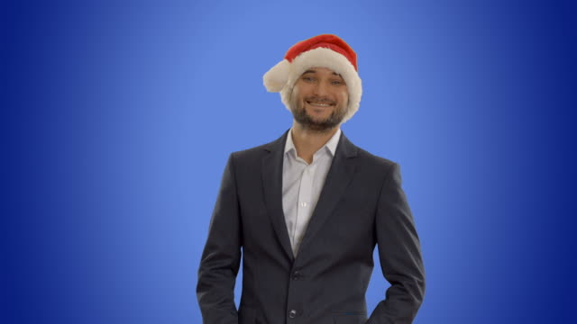 young businessman in hat of Santa Claus on blue background