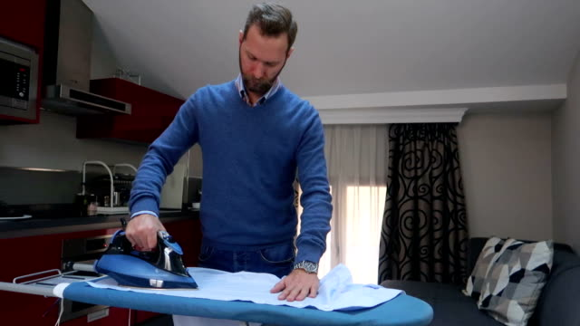 young businessman ironing clothes - stock video - moustache stock videos & royalty-free footage