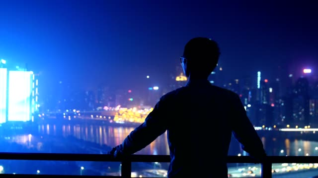 Young businessman looking at city night