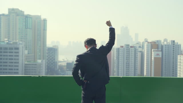 vidéos et rushes de a young businessman making a fist and being happy on the roof - fist