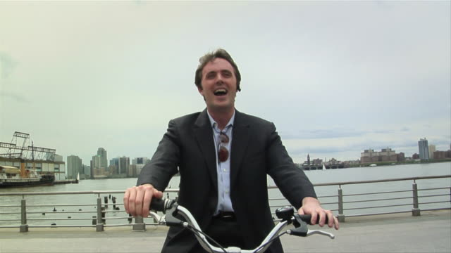 vidéos et rushes de cu, zi, zo, young businessman on bicycle talking on bluetooth headset and cheering, new york city, new york, usa - 25 29 ans