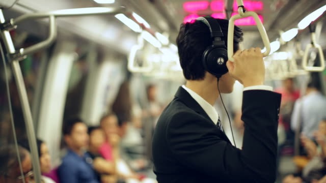MS Young Businessman on subway train using headphones
