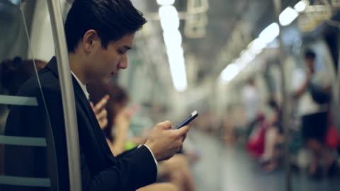 vídeos y material grabado en eventos de stock de cu young businessman on subway train using smartphone - metro transporte