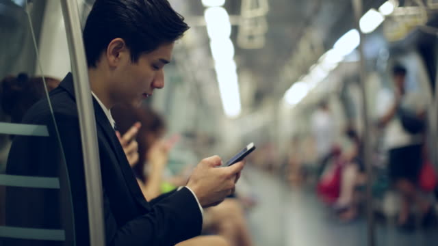 stockvideo's en b-roll-footage met cu young businessman on subway train using smartphone - metro spoorwegvervoer
