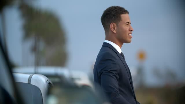 vidéos et rushes de young businessman relaxing against his car - cheveux courts