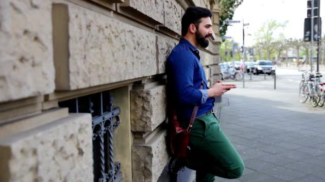 Hombre de negocios joven conteste a texto en móvil