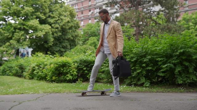 junger geschäftsmann, der skateboard zur arbeit bringt - brille stock-videos und b-roll-filmmaterial