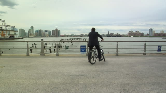WS, Young businessman riding bicycle and talking on Bluetooth headset, river in background, New York City, New York, USA