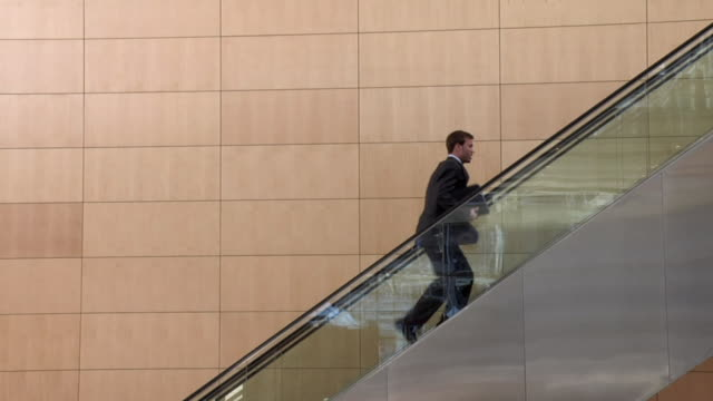 slo mo ws young businessman running up escalator moving down, cape town, south africa - rolltreppe stock-videos und b-roll-filmmaterial