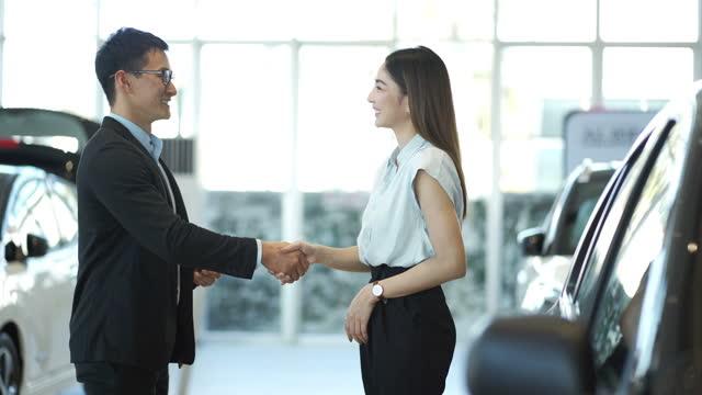 4k giovane uomo d'affari che stringe la mano all'imprenditrice dopo aver fatto un accordo - venditore video stock e b–roll