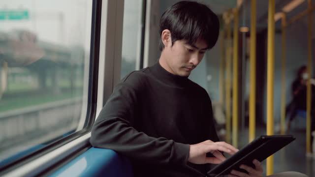 junger geschäftsmann sitzt und arbeitet im zug auf digitalem tablet - bahnreisender stock-videos und b-roll-filmmaterial