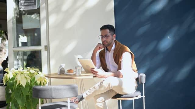 stockvideo's en b-roll-footage met jonge zakenmanzitting bij de staaf en gebruikend een digitale tablet - sunny