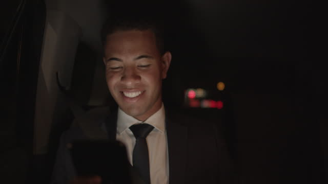 young businessman sitting in a back seat of a car using his phone - person gemischter abstammung stock-videos und b-roll-filmmaterial