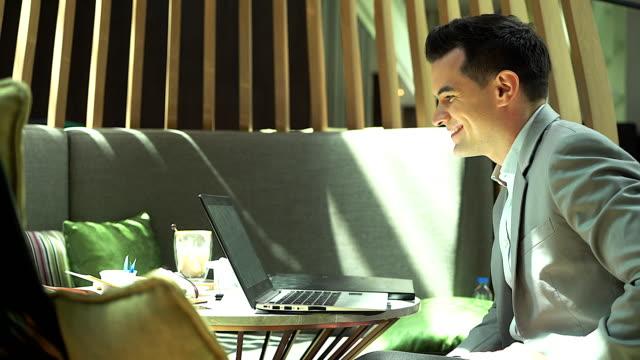 vídeos y material grabado en eventos de stock de hombre de negocios joven sentado en la cafetería durante el uso de ordenador portátil a llamada de conferencia. - voz sobre ip