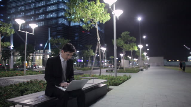 vidéos et rushes de mh ld young businessman sitting on bench working on laptop at night / singapore - costume complet