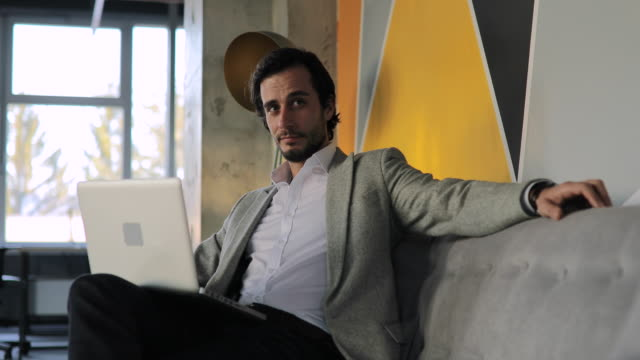 young businessman sitting on sofa in modern office - males stock videos & royalty-free footage