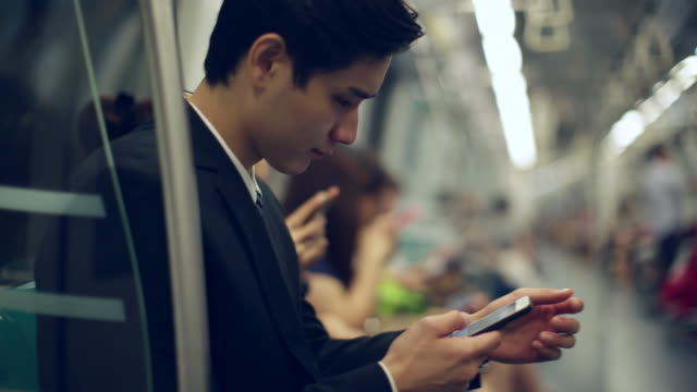 cu young businessman sitting on subway train using smartphone - smart phone video stock e b–roll