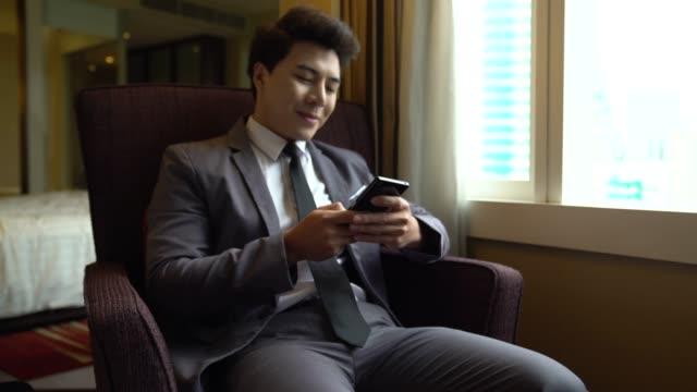 giovane uomo d'affari seduto sulla sedia nella sua stanza d'albergo digitando un messaggio sulla sua tecnologia di mobilità smartphone connettività operatore di viaggio dispositivo di viaggio gadget comunicazione professionale. - offrire un servizio video stock e b–roll