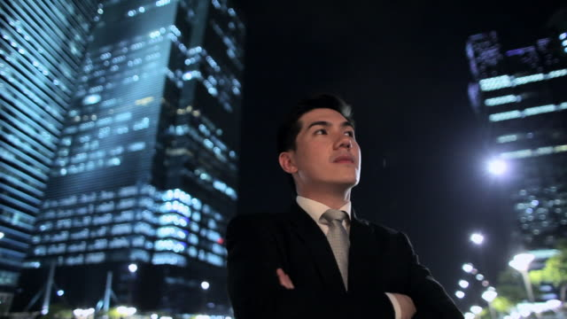 mh la pan young businessman standing in front of buildings at night / singapore - low angle view stock videos & royalty-free footage