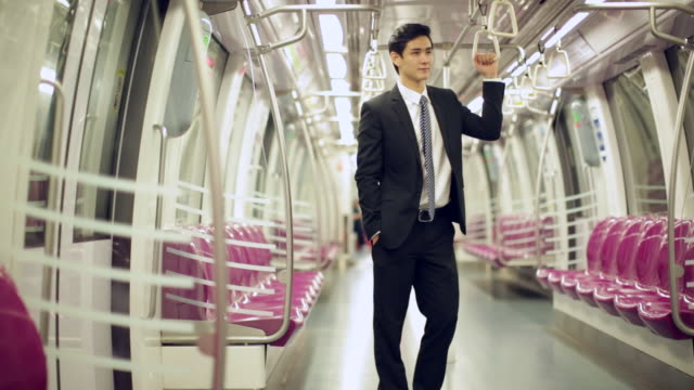 WS Young Businessman standing on subway train