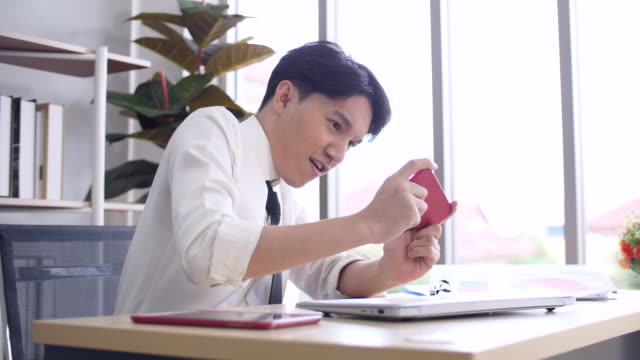 young businessman taking a break by playing game on smart phone at office - toy stock videos & royalty-free footage
