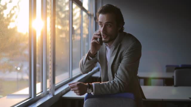 vidéos et rushes de jeune homme d'affaires parlant sur le mobile dans le bureau - seulement des hommes