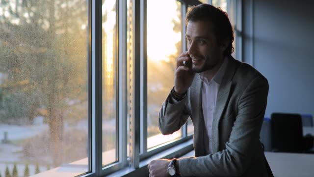 vidéos et rushes de jeune homme d'affaires parlant sur le téléphone portable dans le bureau - seulement des jeunes hommes