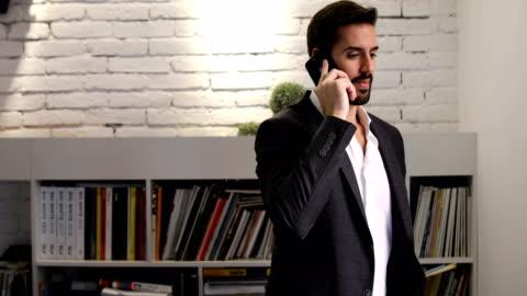 vídeos y material grabado en eventos de stock de joven empresario hablando por teléfono en su oficina - estante muebles