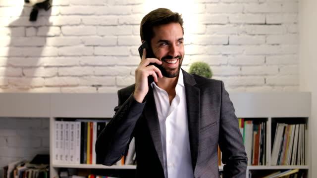 vídeos de stock, filmes e b-roll de jovem empresário falando ao telefone em seu escritório - só um homem