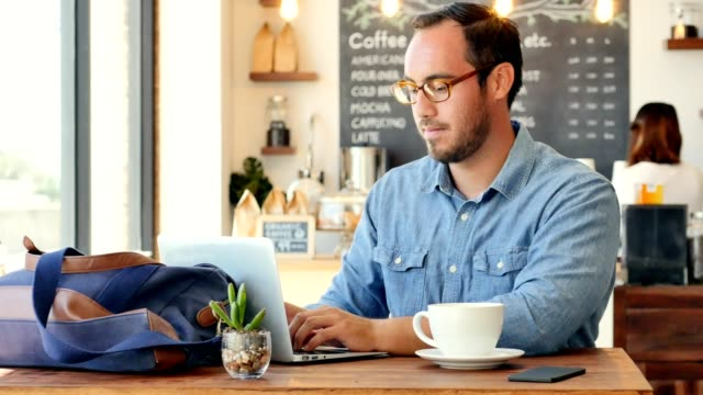Young businessman telecommutes from local cafe