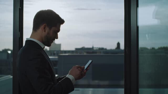 young businessman text messaging on smart phone - back lit stock videos & royalty-free footage