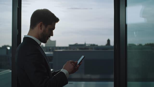 vídeos de stock, filmes e b-roll de mensagem de texto nova do homem de negócios no telefone esperto - só um homem
