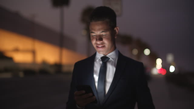 young businessman texting at night in the city - full suit stock videos & royalty-free footage