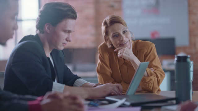 young businessman types on his laptop as businesswoman chats with colleagues - brainstorming stock-videos und b-roll-filmmaterial