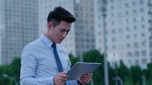 young businessman using digital tablet,4k - skjorta och slips bildbanksvideor och videomaterial från bakom kulisserna