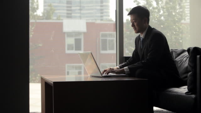 ms young businessman using laptop in office in front of window / china - using laptop stock videos & royalty-free footage