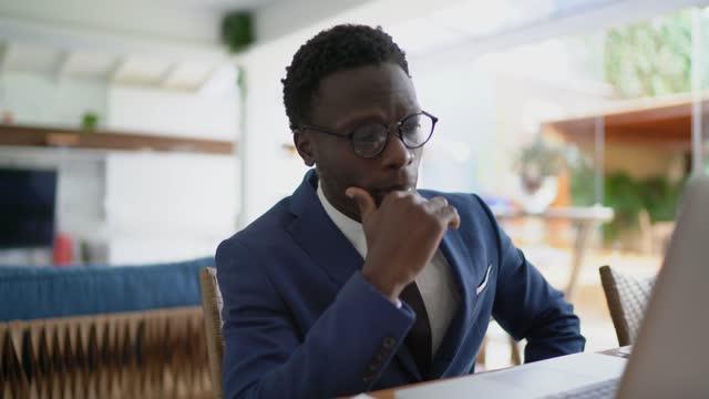 vídeos y material grabado en eventos de stock de joven empresario que usa una computadora portátil trabajando en casa - un solo hombre de mediana edad