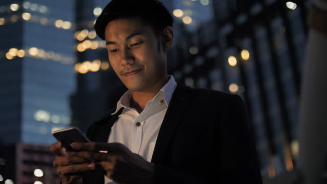 young businessman using phone at night - equipment stock videos & royalty-free footage